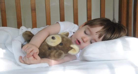 ребенок с игрушкой спит в кроватке