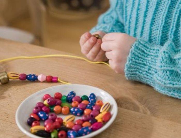 ребенок сидит за столом и нанизывает бусинки
