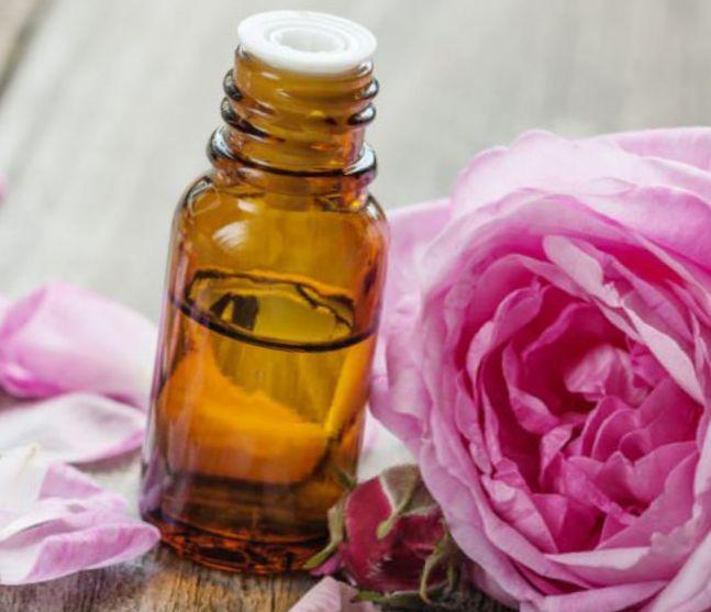 пузырек с розовым маслом и лепестками роз